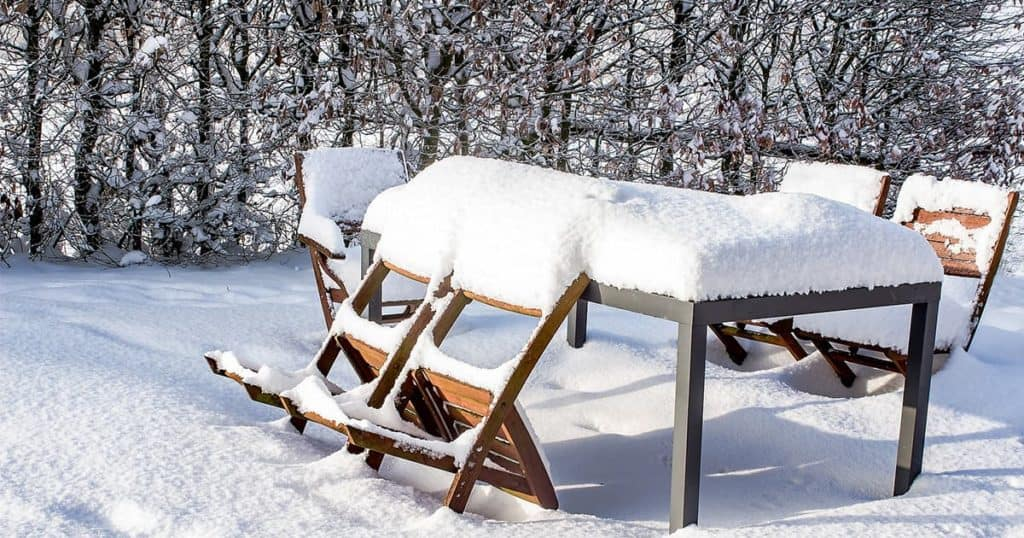 Outdoor table and chairs covered in snow